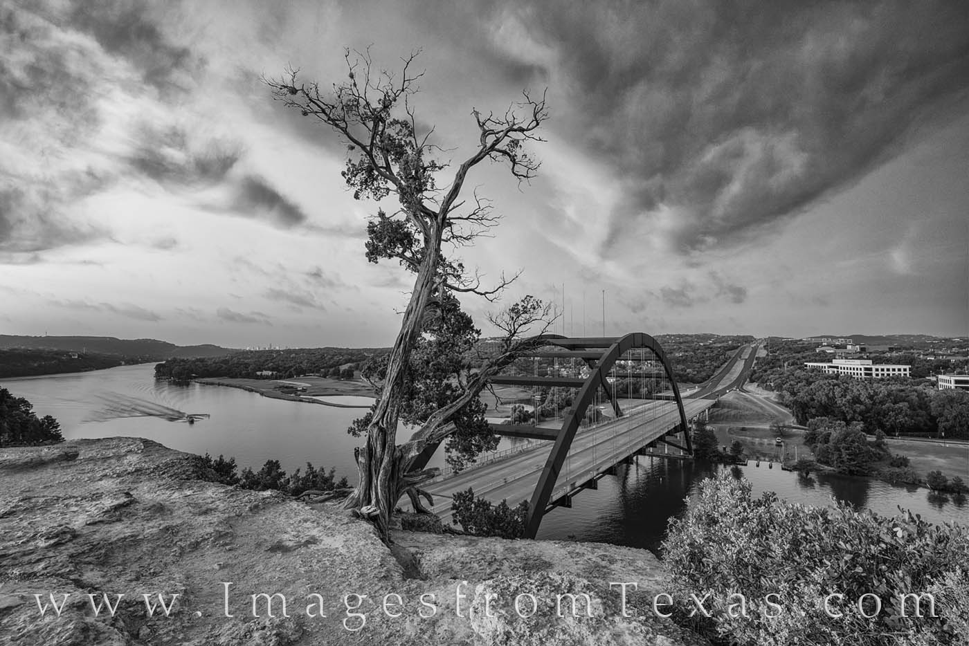 This black and white image shows the iconic Pennybacker Bridge on a beautiful sunrise in July.