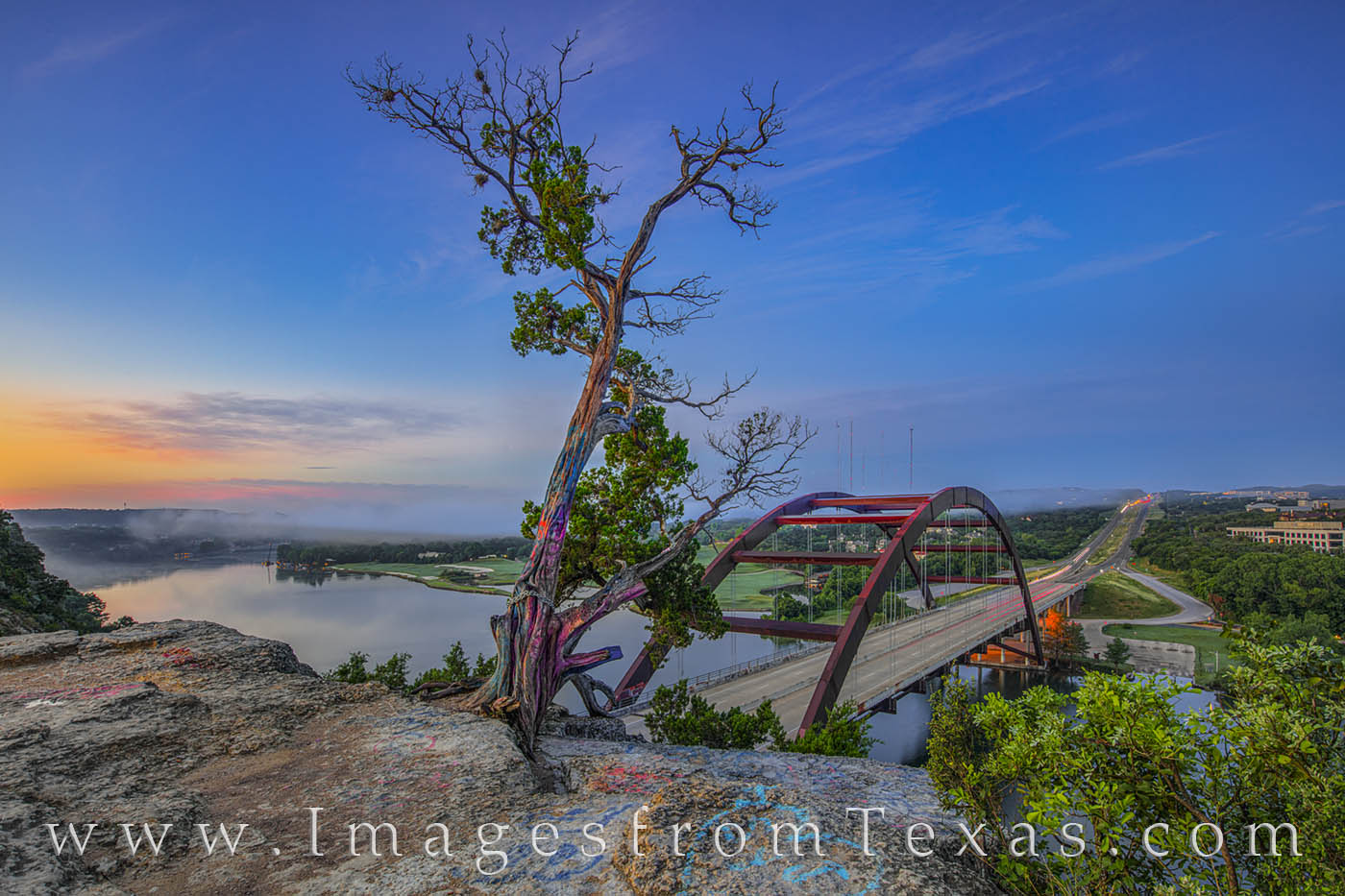 High clouds and low fog fill the air over the Colorado River and Pennybacker Bridge (360 Bridge). From the cliffs overlooking...