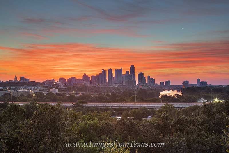 Looking east toward the downtown Austin skyline on a beautiful October morning, the sky is filled with brilliant reds and oranges...