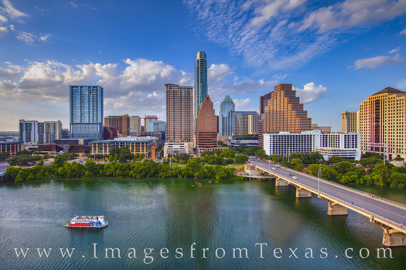 On a late summer afternoon, the Texas Lone Star tourist boat floats along Ladybird Lake. In the distance, the skyline rises into...