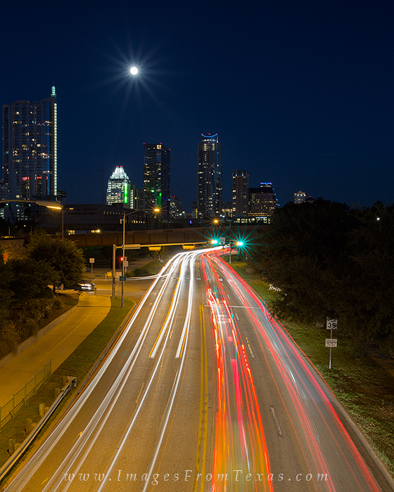 On a night over downtown Austin with a full moon rising, traffic flows east and west on Caesar Chaves, as seen from the Lamar...