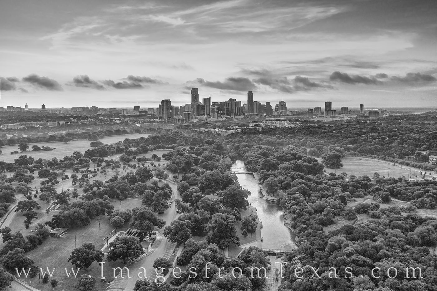 Barton Springs Pool rests far below in this black and white image taken with a high-flying drone. In the distance, the skyline...