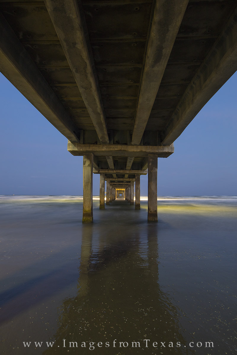 This abstract of Caldwell Pier along the beach at Port Aransas shows the architecture beneath the pier. Above me, folk use the...