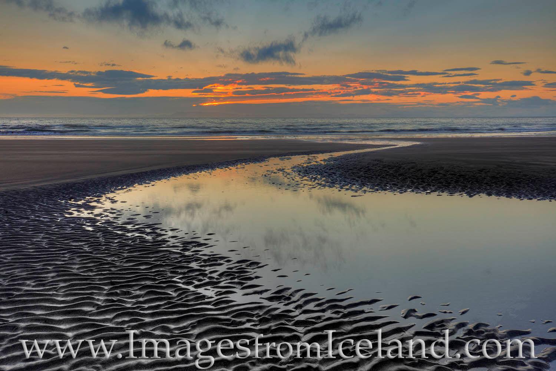 A small stream of water winds its way through a black sands beach to the Atlantic Ocean. Not far from Grundarfjörður, this...