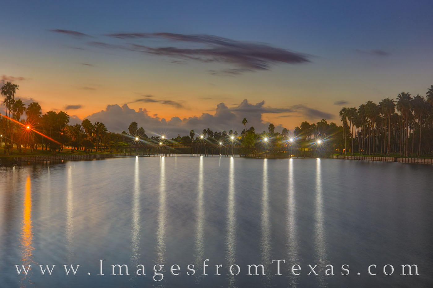 Well before sunrise, distant storm clouds over the Gulf of Mexico loom in the morning sky. This resaca in Brownsville is calm...