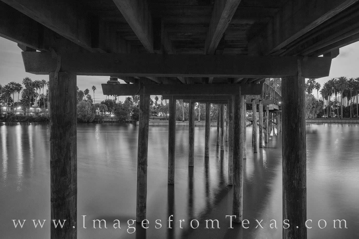 This black and white photograph from Brownsville, Texas, shows an old wooden bridge that spans a resaca. The sturdy pillars hold...