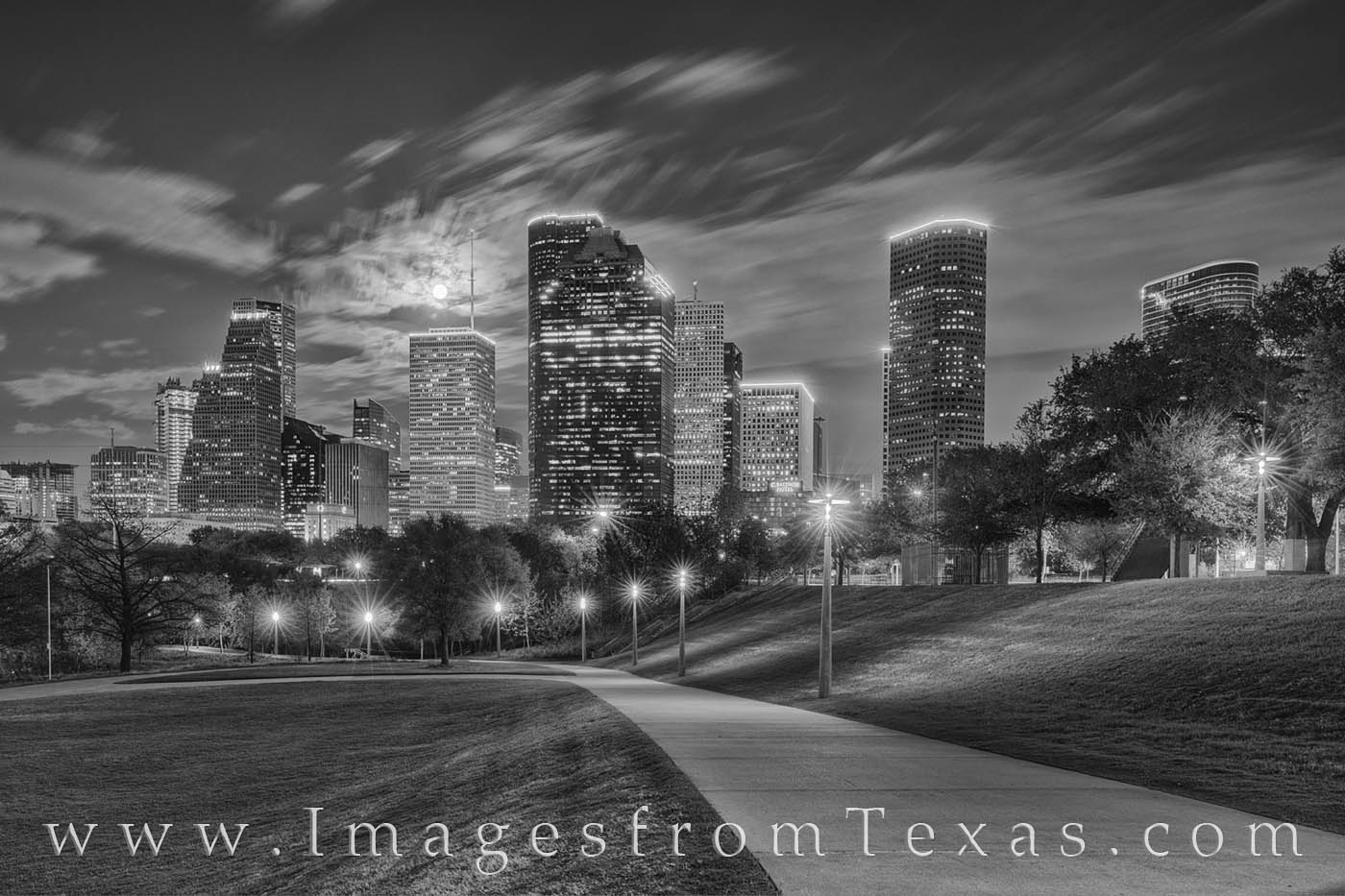 A full moon rises over the downtown high rises of Houston, Texas, on a beautiful spring night. The buldings were glowing with...
