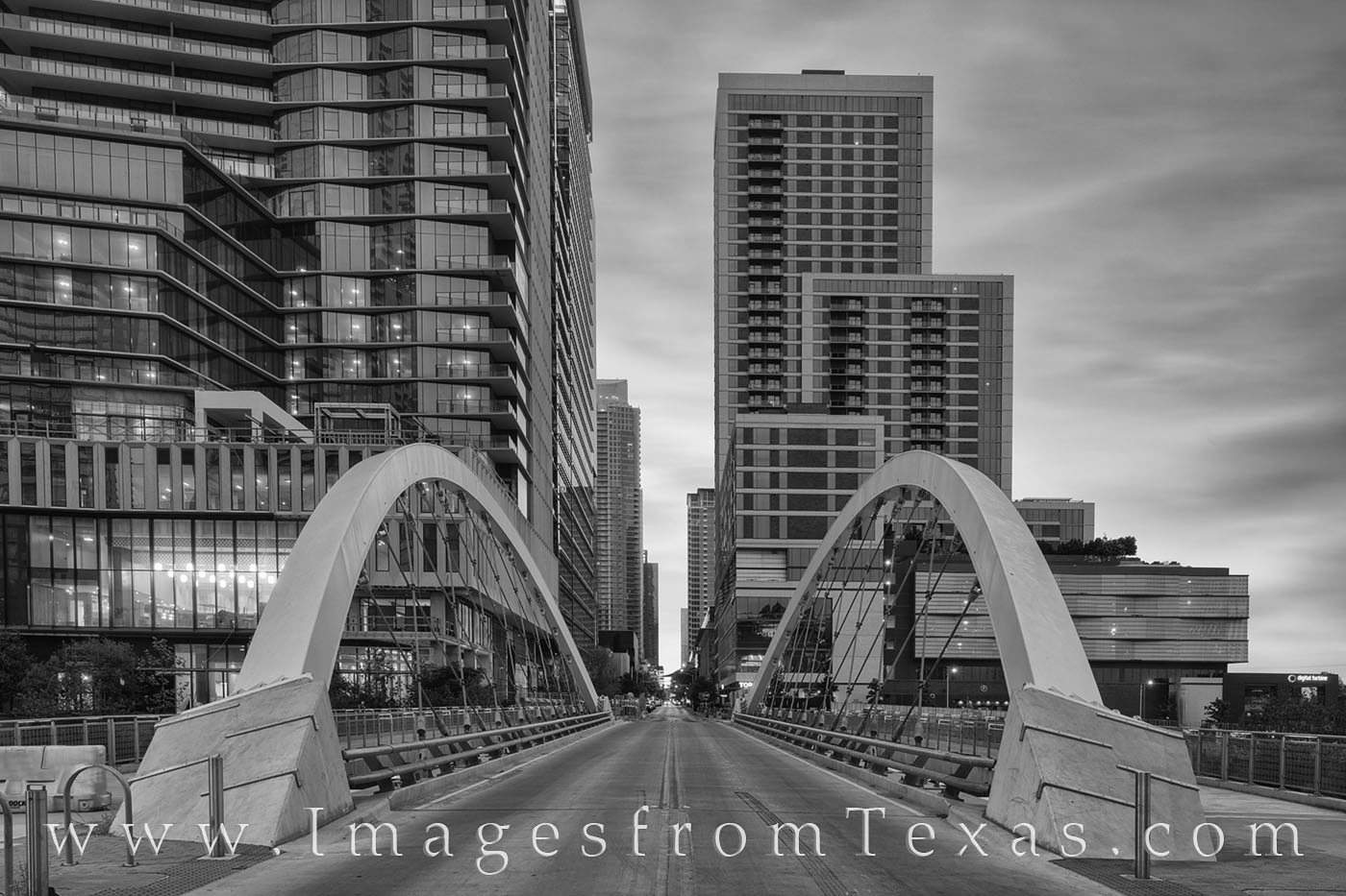 This black and white image from Austin, Texas, shows the Butterfly Bridge. This small bridge is found on 2nd Street as it crosses...