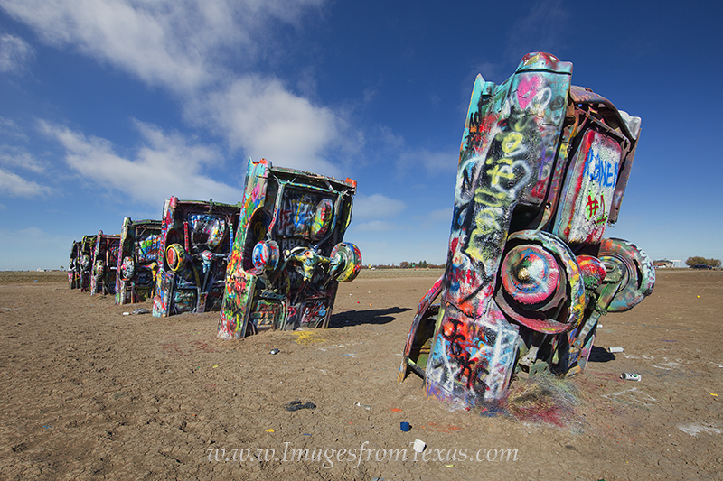 From a different angle, this is the Cadillac Ranch, a permanent art exhibit outside of Amarillo, Texas, on Route 66. A group...