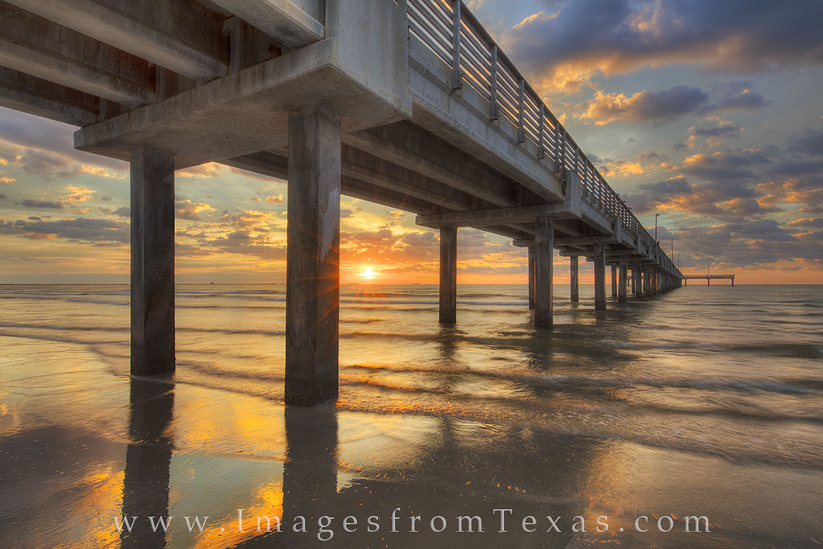 From the west side of Caldwell Pier along the beach at Port Aransas, the sun breaks through the clouds and pillars, turning the...