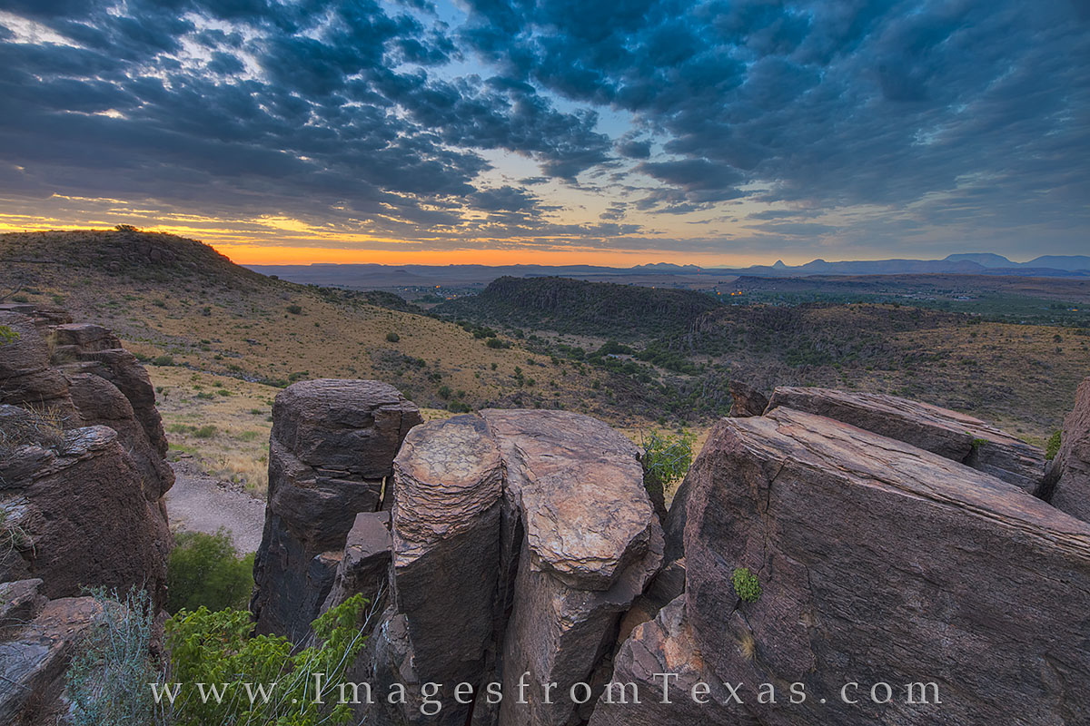 Sunlight begins to break through the clouds and light up the morning in the Davis Mountains. In the distance, Fort Davis awakens...