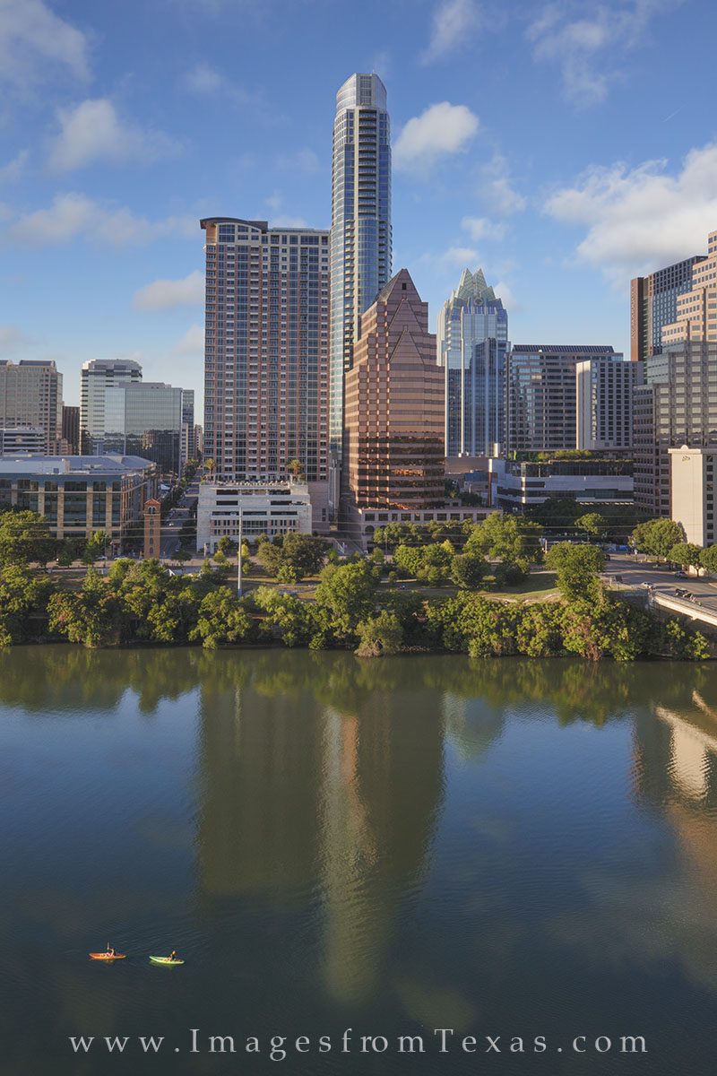 In the reflections of the Austin high rises, two kayakers make their way across Lady Bird Lake on a perfect late spring afternoon...