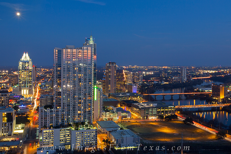 This photograph of downtown Austin looks east at the 360 condos and Frost Bank Tower. To the south is Lady Bird Lake as evening...