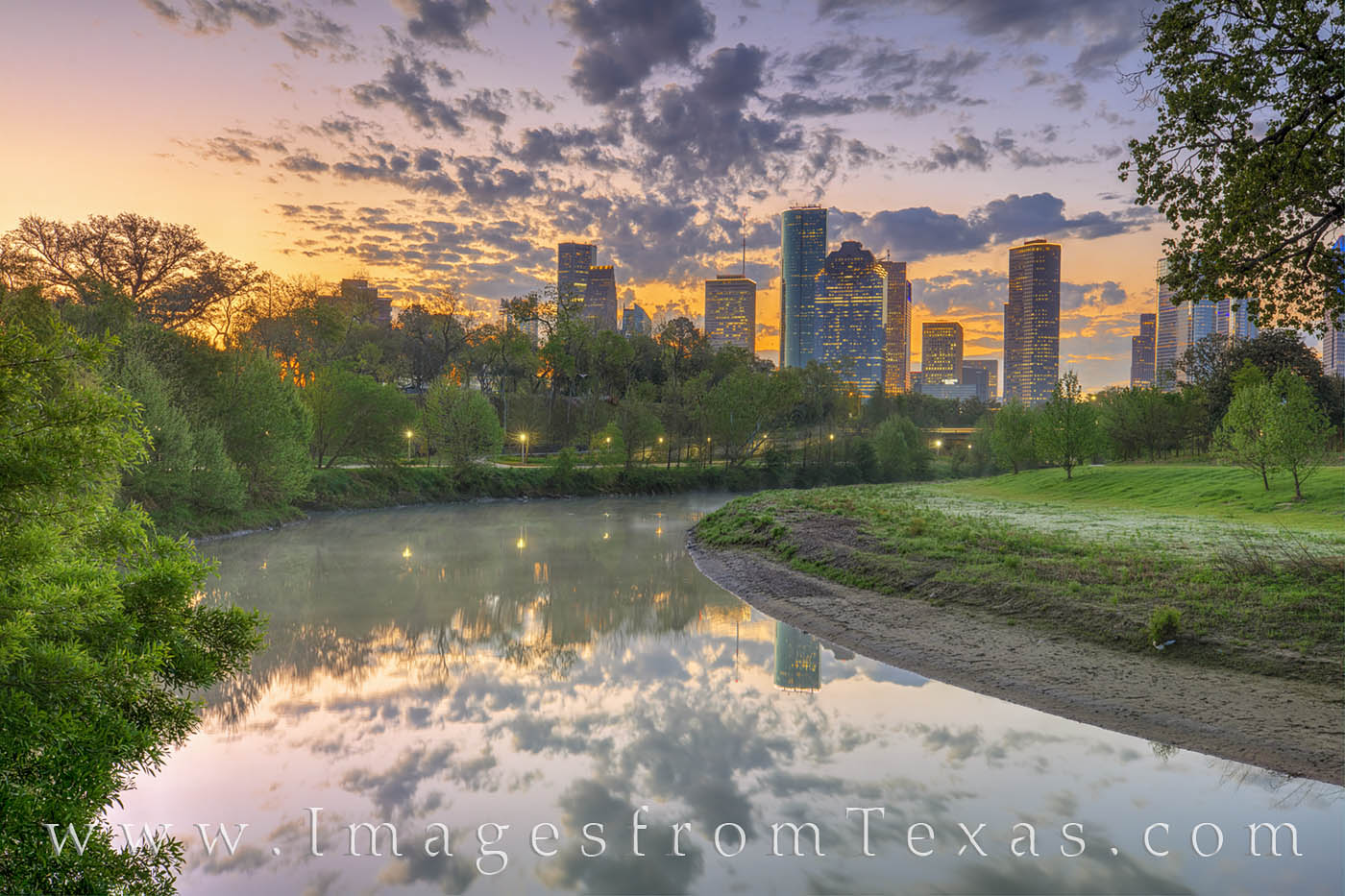 An orange glow on the horizon signal the beginning of a new day near downtown Houston, Texas. The reflection of the skyline along...