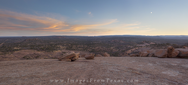This panorama shows Enchanted Rock with soft pastel skies overhead.