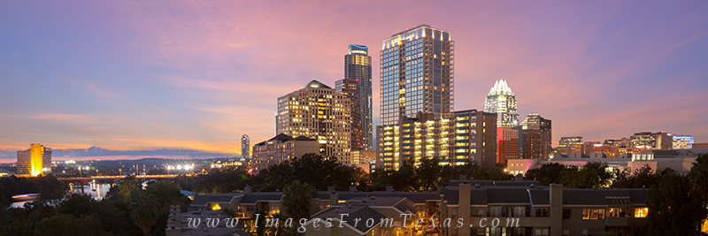 Clouds fill with pink and blue as the sun sets low into the horizon in this panorma over the Austin cityscape. In the distance...