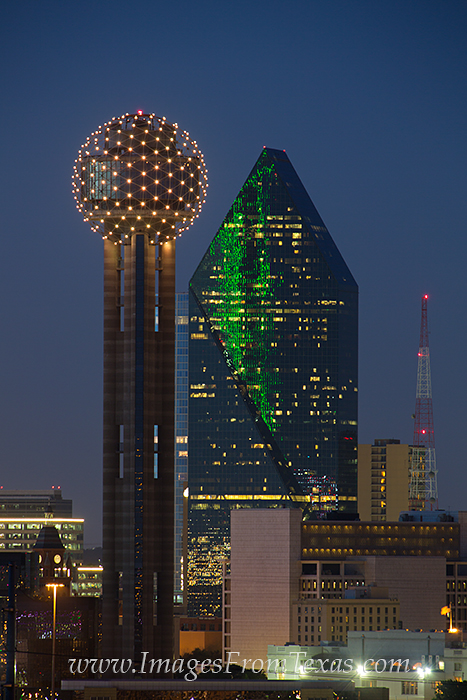 Reunion Tower and Fountain Place light up at night as part of the Dallas cityscape.