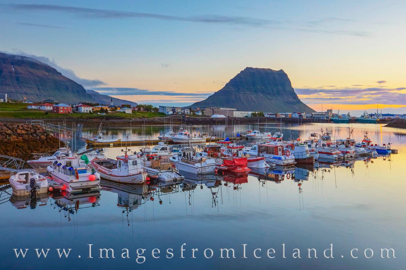 The well-known Kirkjufell Mountain looms over the peaceful Grundarfjörður Harbor in the never-ending daylight of a summer...