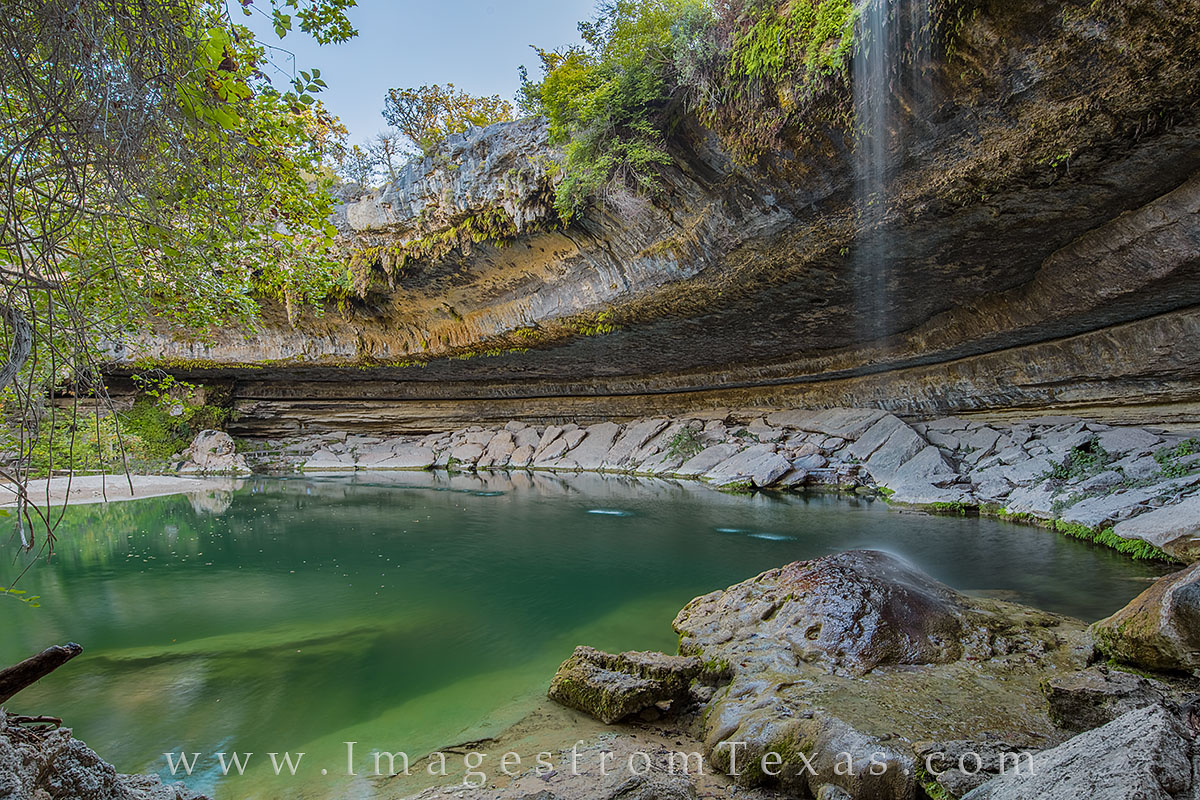 From the side of the Hamilton Pool grotto, this view looks across the emerald waters of this gem in the Texas Hill Country on...