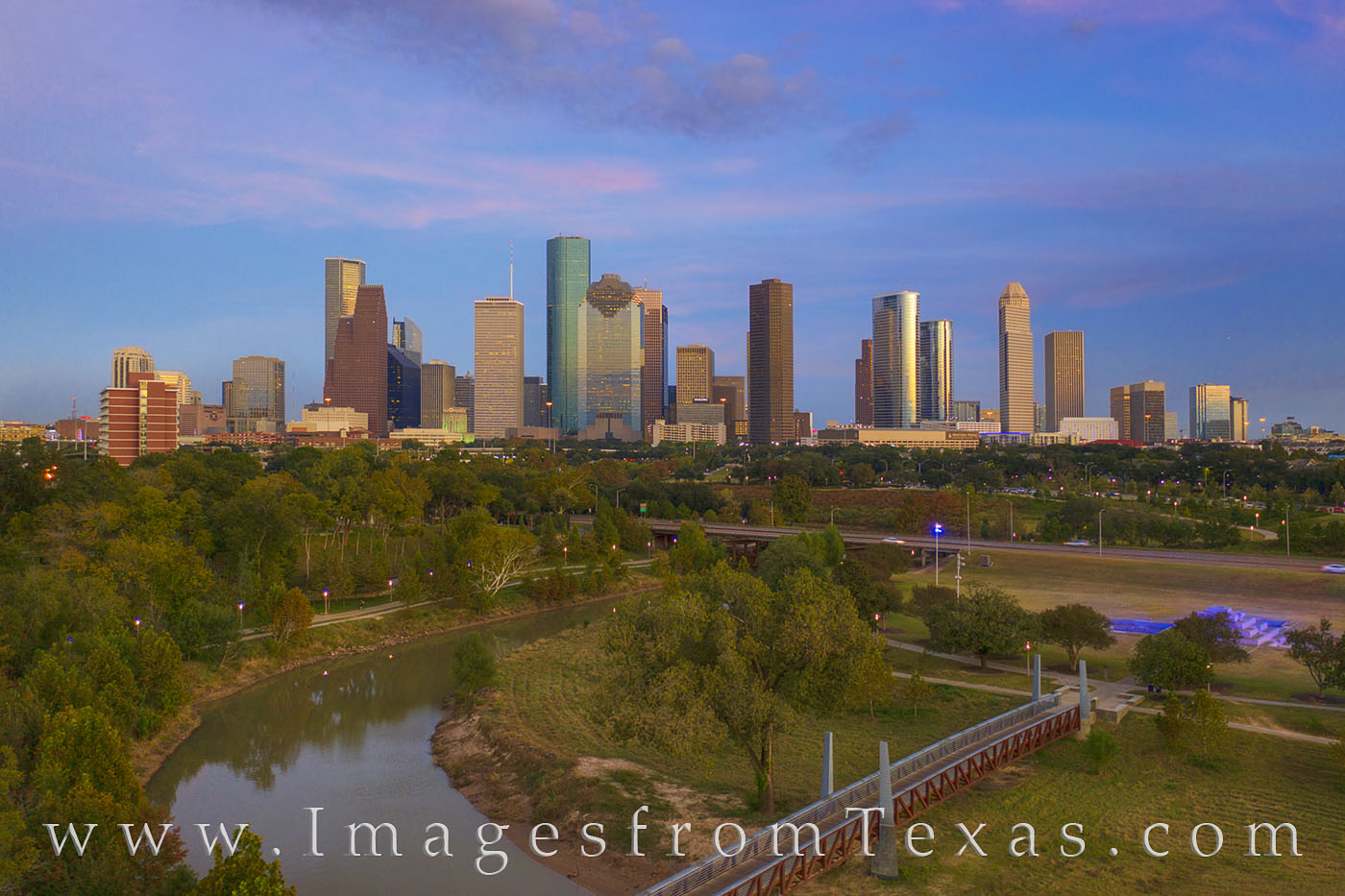 Soft pastel clouds drift lazily across the evening skyline in Houton, Texas. Down below, Buffaly Bayou winds and curves through...