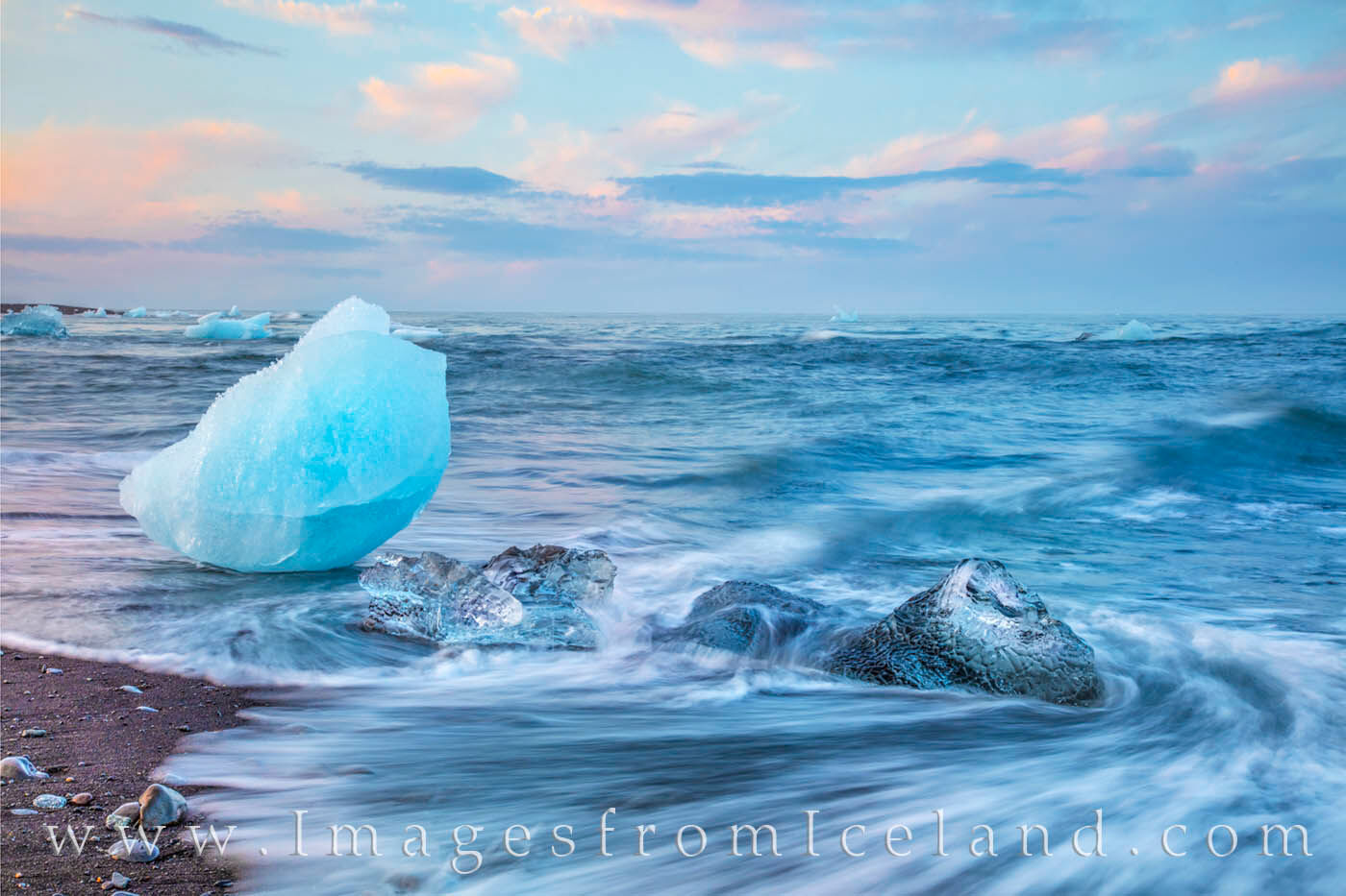The swirling waves of the North Atlantic Ocean wash up icebergs onto Diamond Beach. These beautiful chunks of ice break off from...