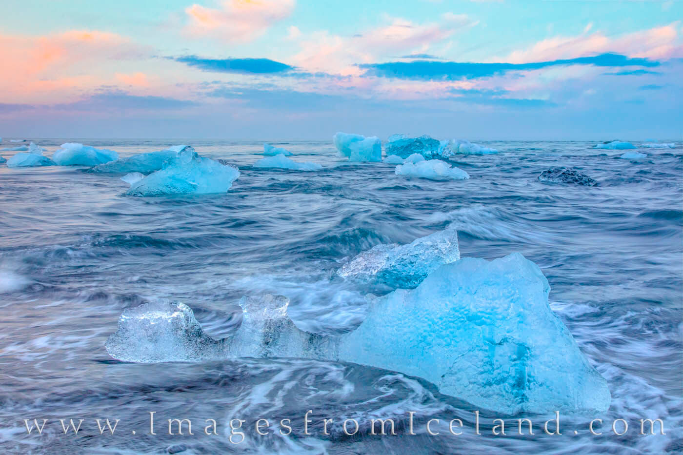The deep, aqua-blue colors of icebergs along the black sands of Diamond Beach show off their colors beneath the pastel shades...