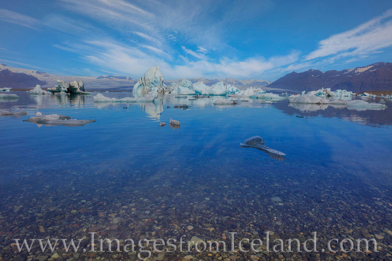 Icebergs float in the quiet morning in Iceland's Jökulsárlón Bay. Periodically, chunks of ice break off from Breiðamerkurj...