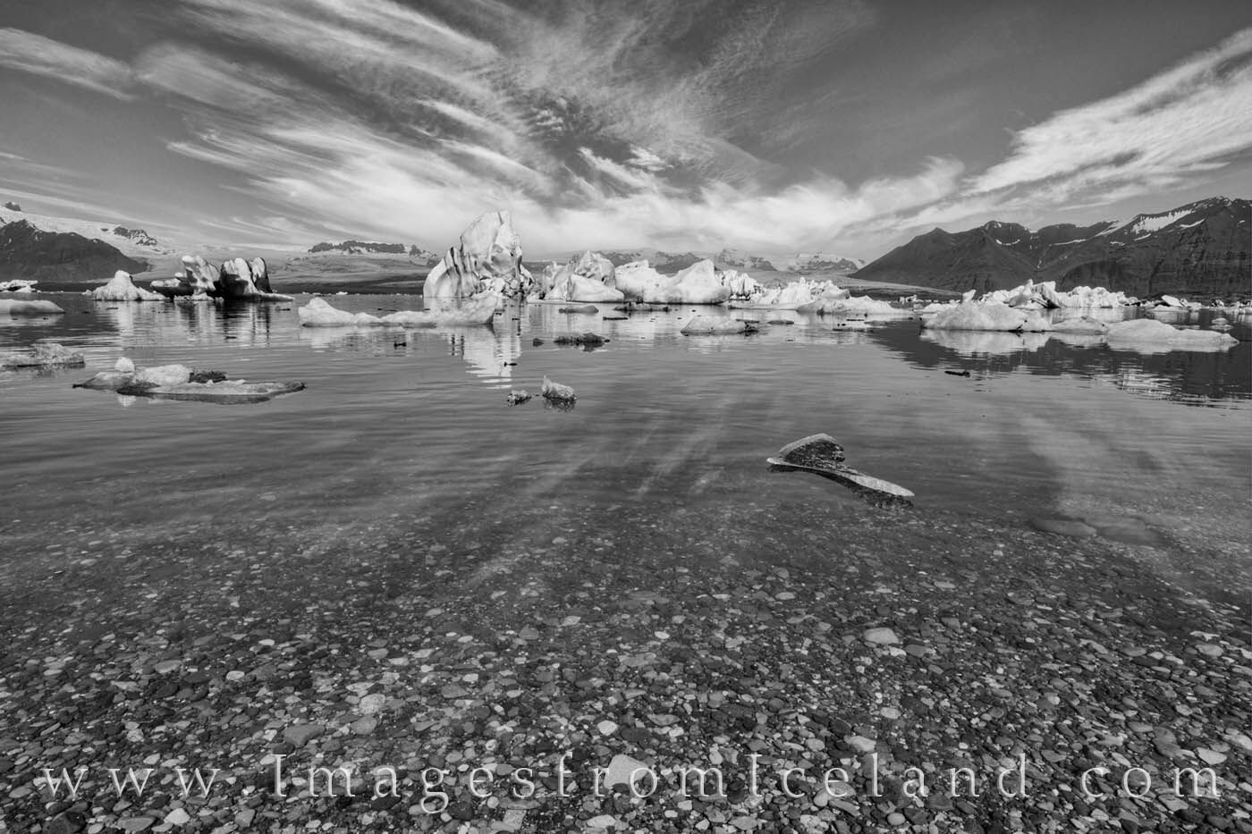 Icebergs from Breiðamerkurjökull Glacier float under a summer sky and clouds in this black and white image from south Iceland...
