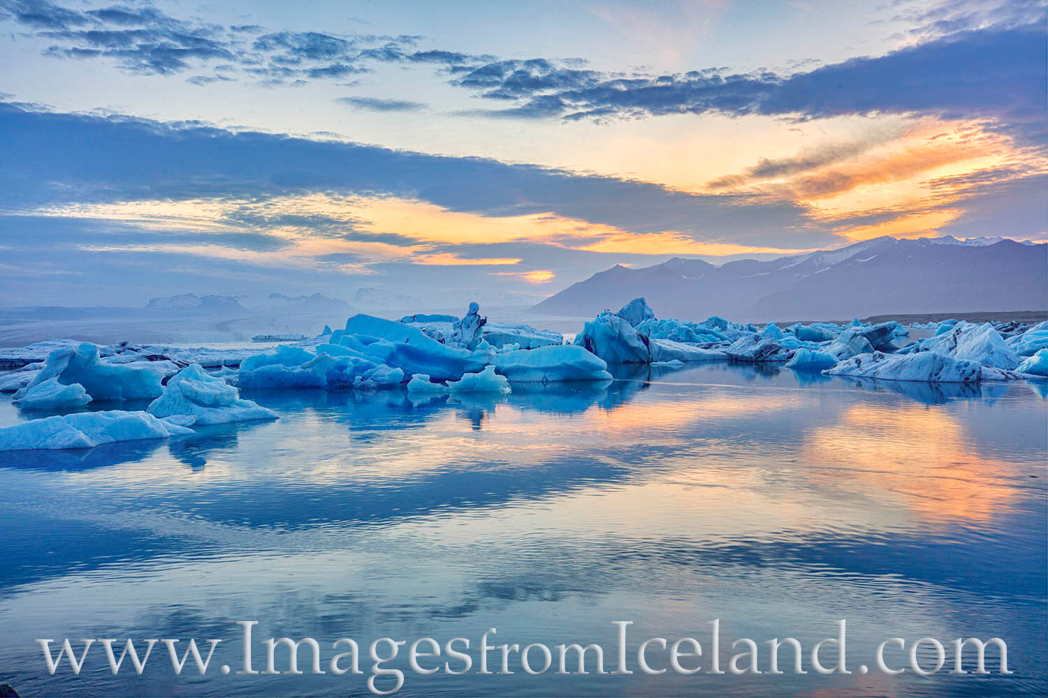 In the soft light of the midnight sun, Jökulsárlón Bay, also known as Glacier Bay, is bathed in soft blue hues. Ice breaks...