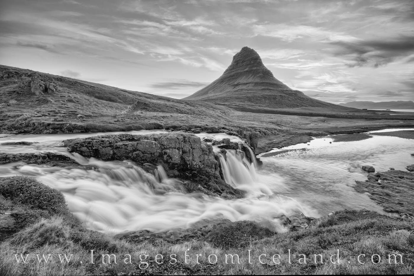 A little before sunrise, the skies above Kirkjufell Mountain show some soft pastel designs. The water of Kirkjufellfoss flowed...