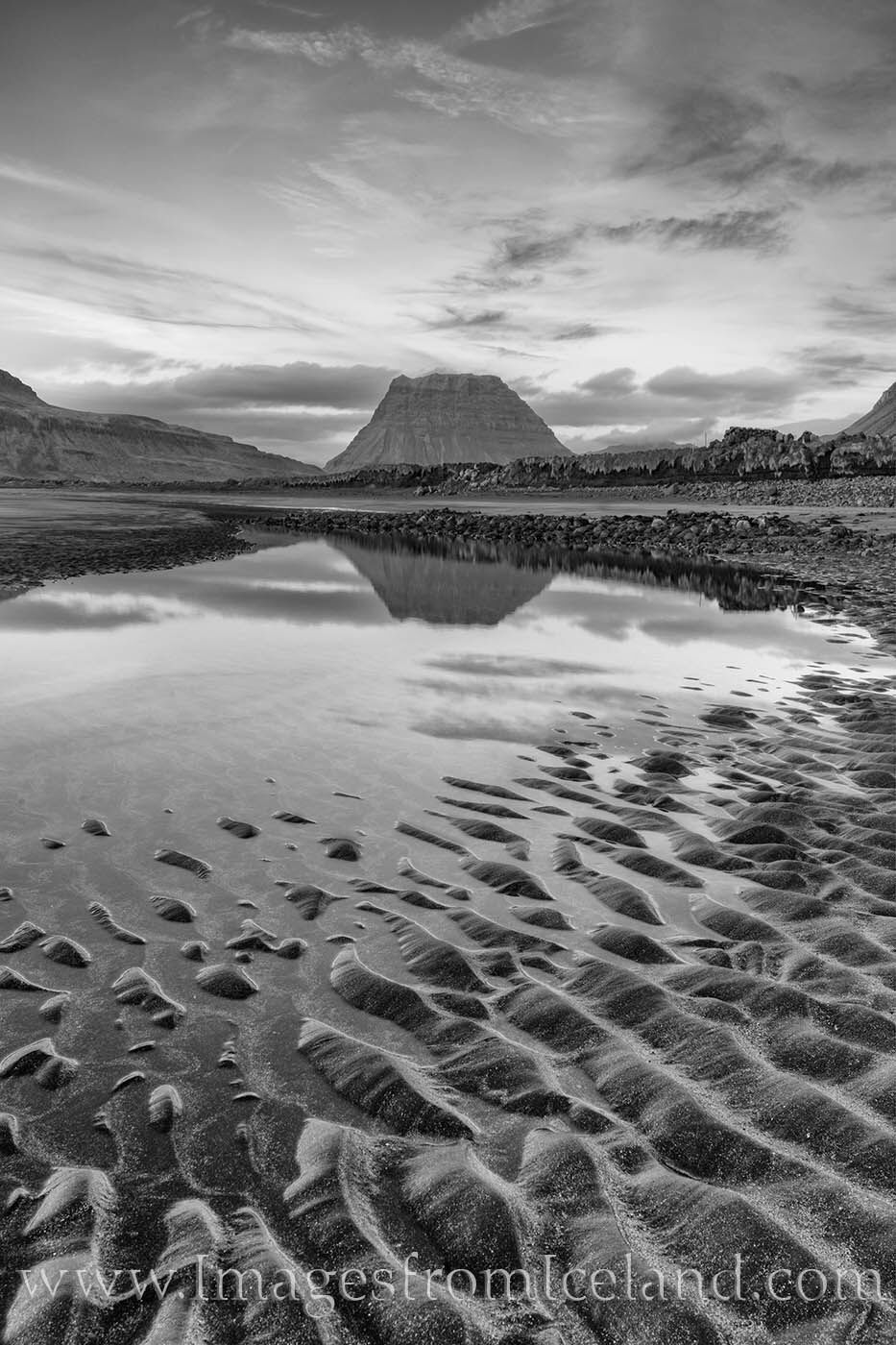 Kirkjufell sits in the midnight light of summer in this black and white image. Taken from a black sands beach just west of this...