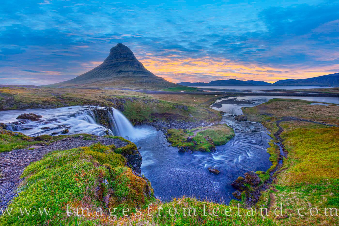 The Kirkjufellsá River flows down from a volcano named Helgrindur, past Kirkjufell Mountain, and into Grundarfjörður Bay and...