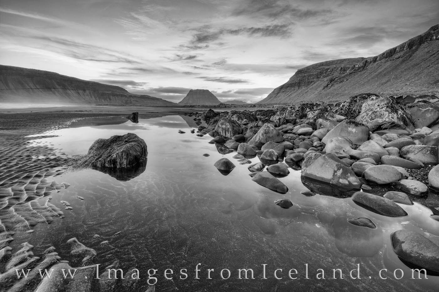 From a black sands beach just west of Kirkjufell Mountain, this black and white image shows the magnificient landscape on a cool...