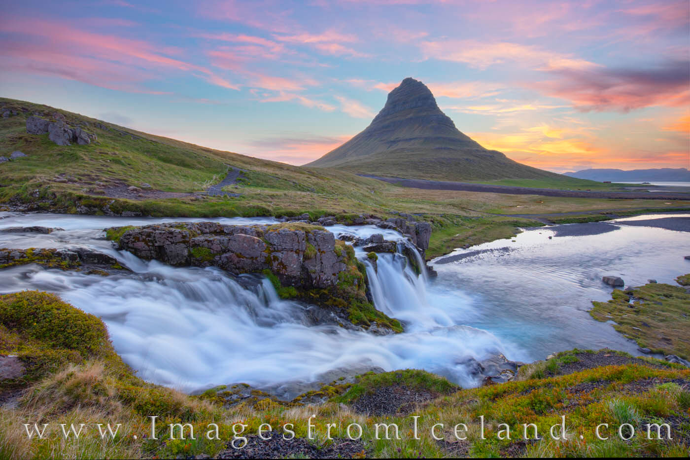 The Kirkjufellsá river tumbles over cascades in the early morning light of summer. Kirkjufell Mountain, also known as Church...