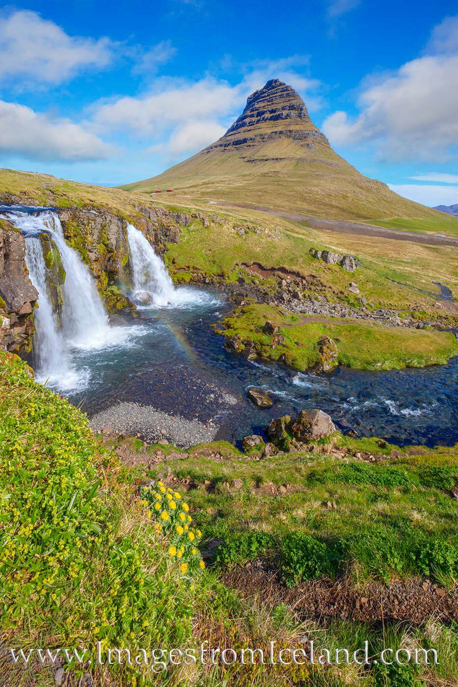 Kirkjufellfoss flows clean and clear in the shadow of Kirkjufell Mountain (also known as Church Mountain). Kirkjufell is the...