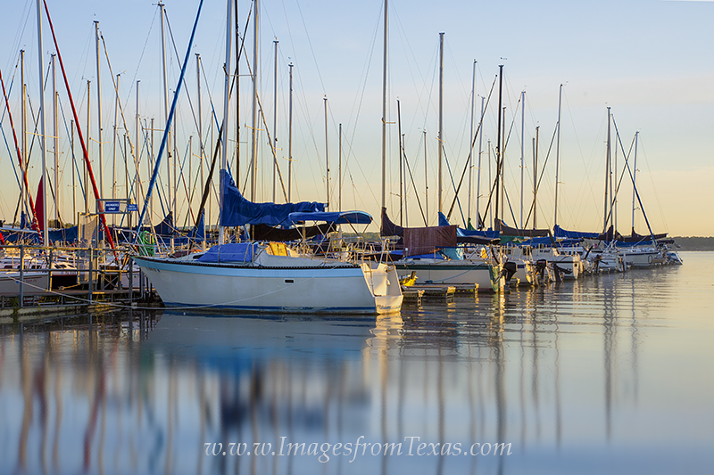 Just after sunrise, the boats in a little harbor on Lake Travis rest in the still morning. This little sanctuary on the edge...