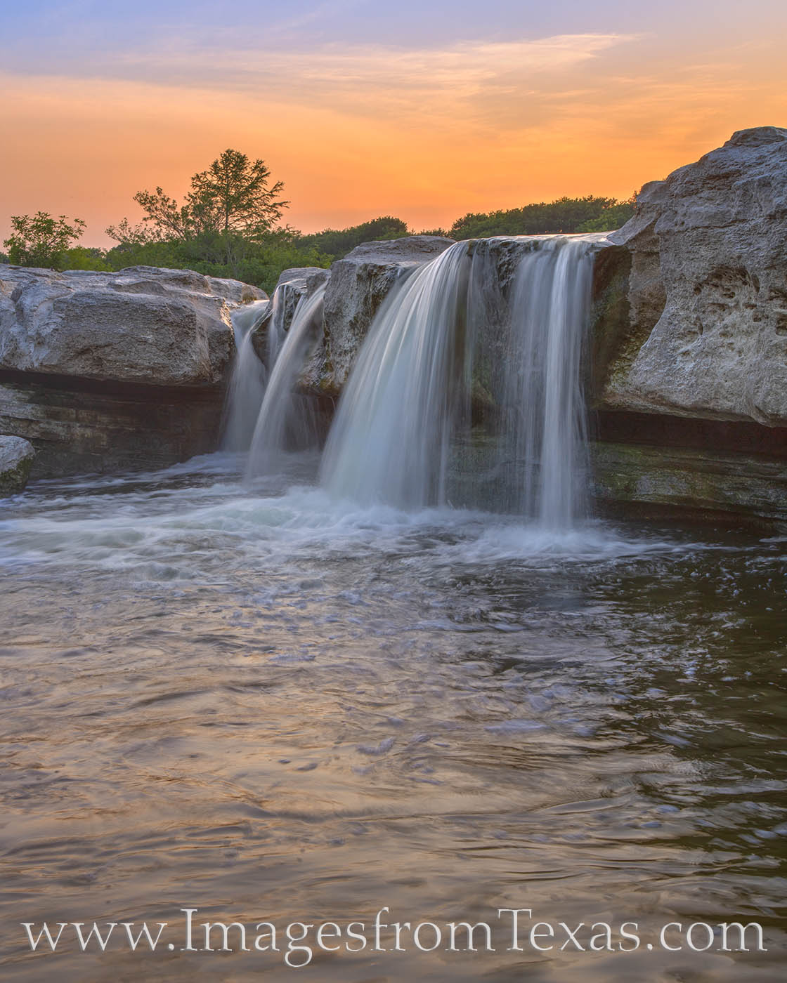 The beautiful and silky cascade of Lower Falls at McKinney Falls State Park shows off its beauty on a colorful evening in late...