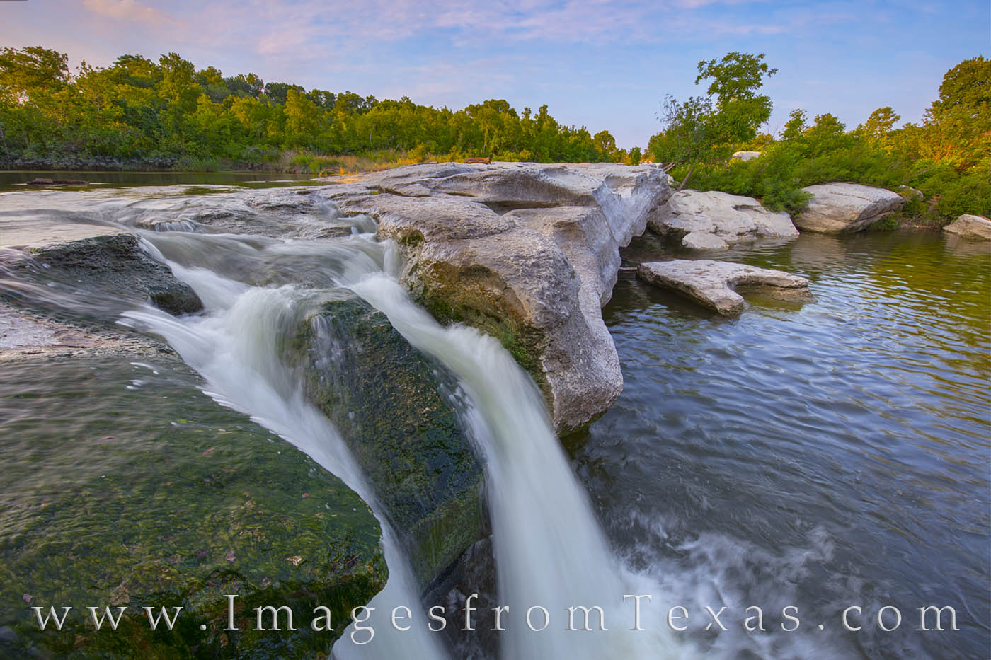 Fast flowing water from Onion Creek pours over the limestone rocks at the Upper Falls area of McKinney Falls State Park in the...