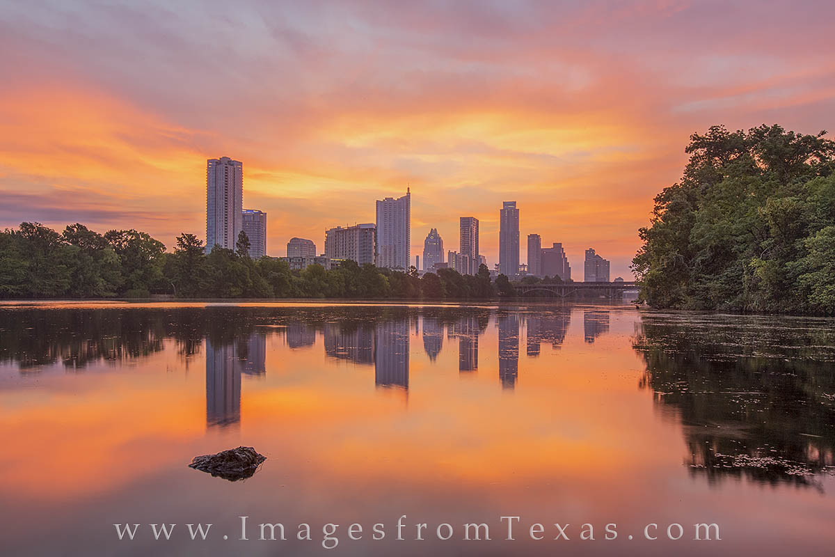A glorious sunrise spreads orange and pink light across downtown Austin, Texas, and Lady Bird Lake. The waters were smooth and...