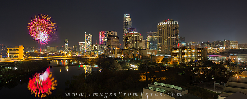 On New Year's Eve, fireworks explode over Lady Bird Lake on the last day of a Cold December night. The buildings of the Austin...