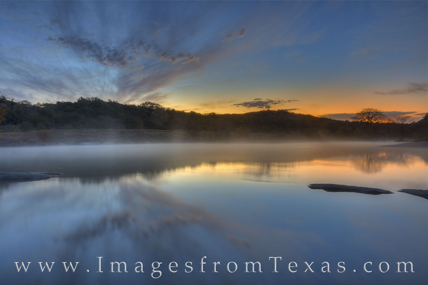 Well before sunrise, the sky turns blue and orange as the first glow from the sun's light brings light to the Pedernales River...