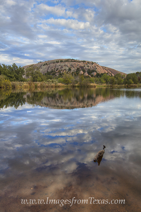 This vertical image shows Enchanted Rock on a beautiful late November afternoon. With Moss Lake in the foreground, the Texas...