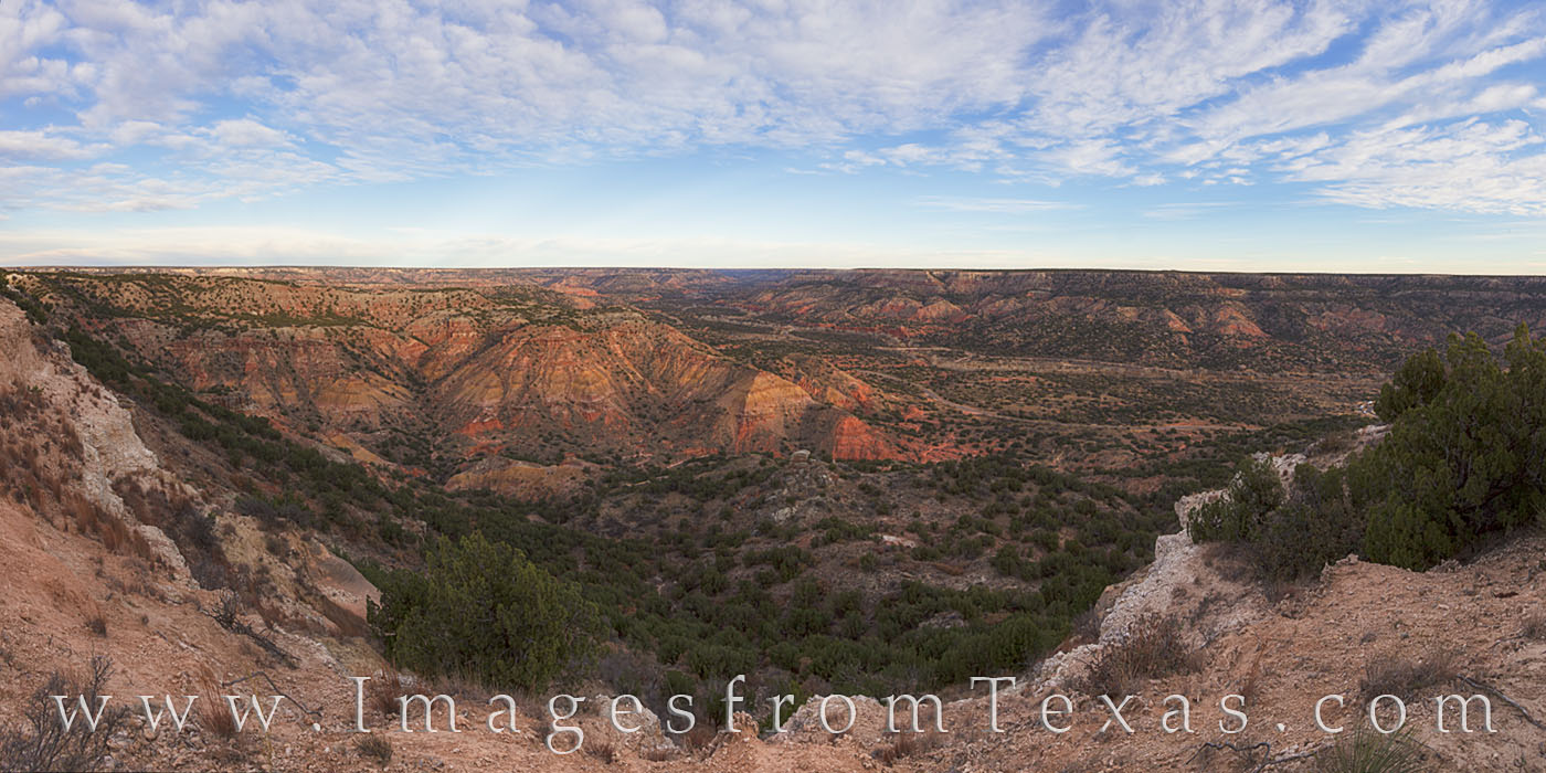 From the rim of Palo Duro Canyon, this panorama looks over the red and orange rock of the distant cliffs and across the valley...