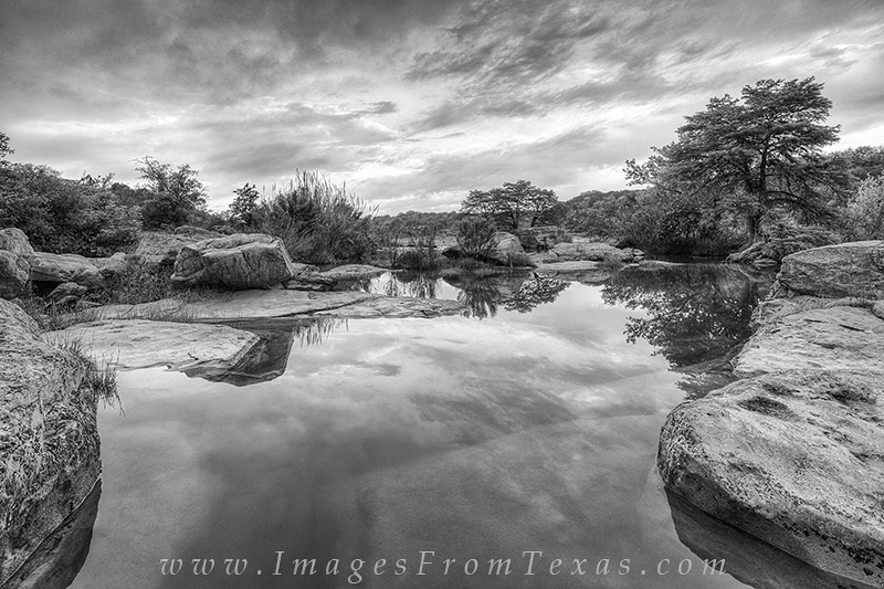 On a still April morning in the Texas Hill Country, this black and white photograph shows the pools of Pedernales Falls State...