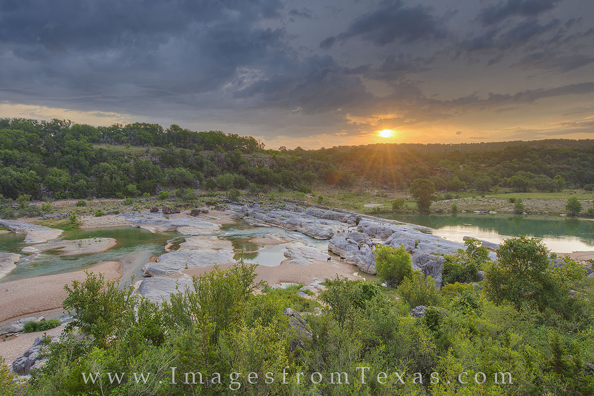 The sun breaks through low clouds of a fading storm on a June morning in the Texas Hill Country. This view shows the river valley...