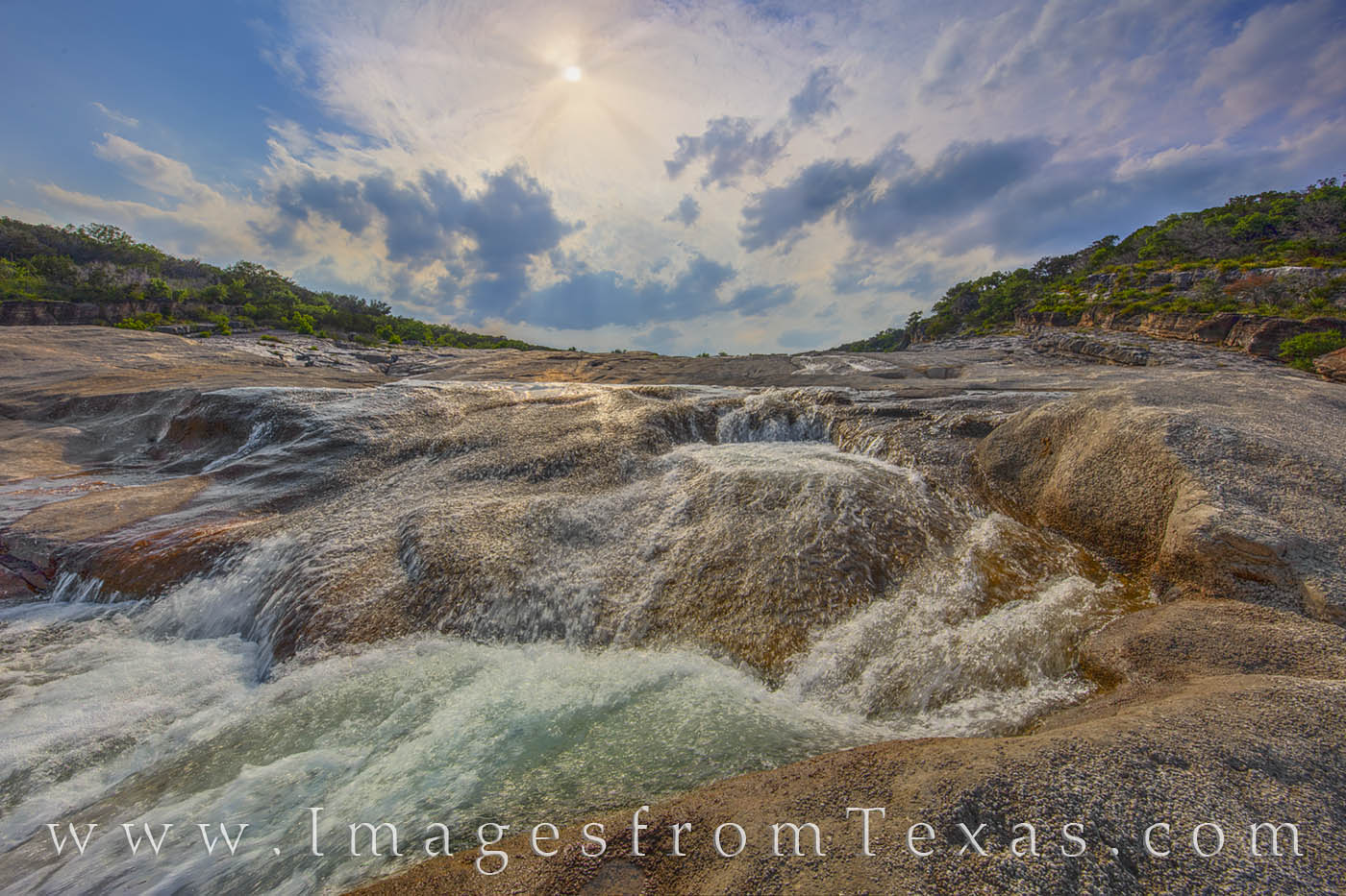 With the sun hiding behind a thin layer of clouds, the Pedernales River flows over a limestone basin through Pedernales Falls...