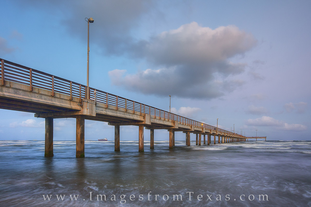 Soft clouds glow pink and blue in the late evening over Caldwell Pier. This fishing bridge juts out from the beach at Port Aransas and nearly always has people on it fishing and enjoying the ocean lif, photo