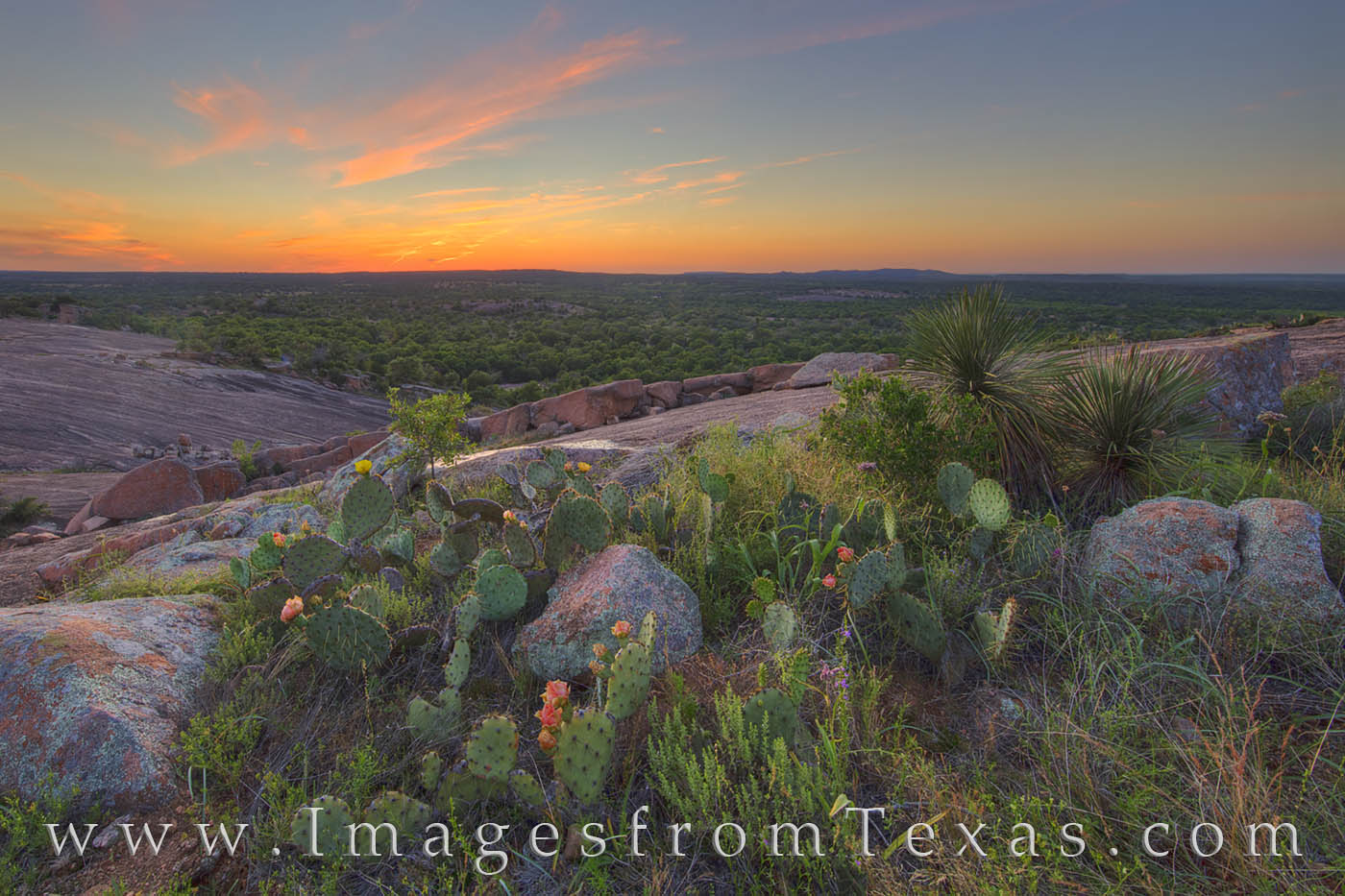 On a very still evening one of the Texas Hill Country's iconic locations, Enchanted Rock, the evening sky lights ends the day...