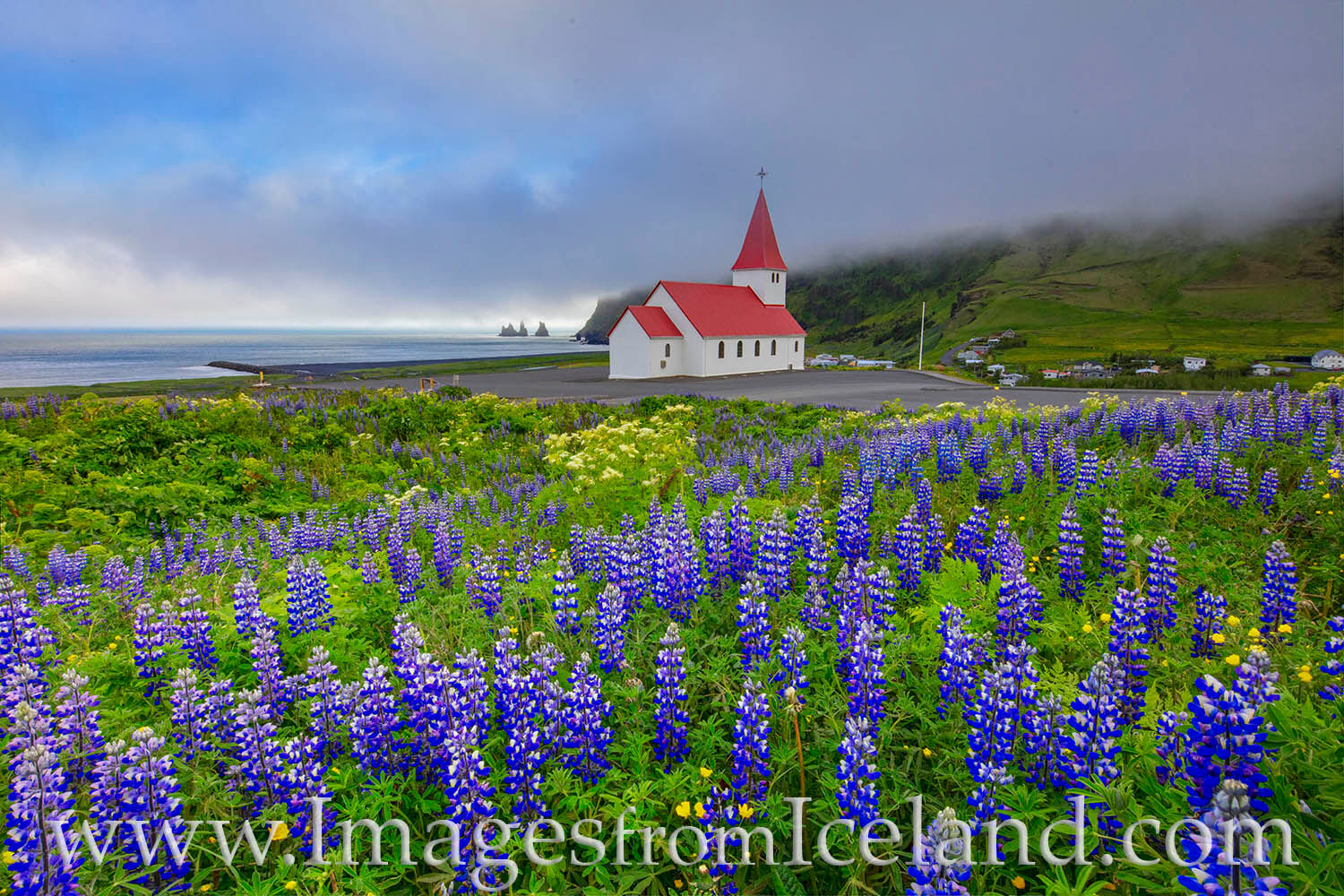 In south Iceland atop the village of Vík í Mýrdal, a little white church wth a red roof sits atop the hill. Reyniskirkja is...
