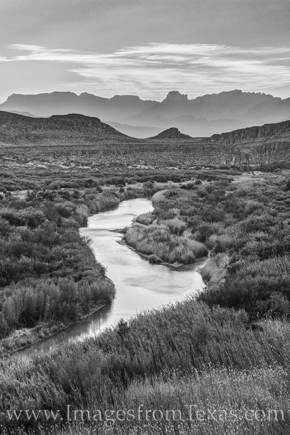 The Rio Grande flows eastward toward the Gulf of Mexico in this black and white photograph from Big Bend National Park. The rugged...